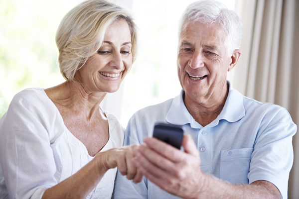 Shot of a senior couple reading a text message together at home