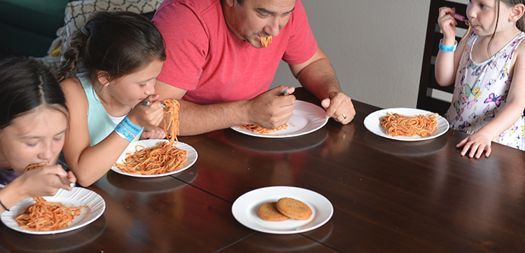 family eating spaghetti dinner